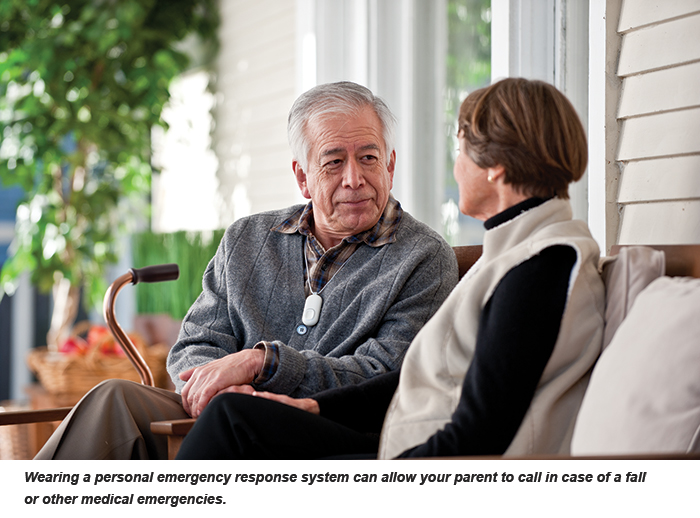 A pair of seniors converse on a porch; the man wears personal emergency device around his neck