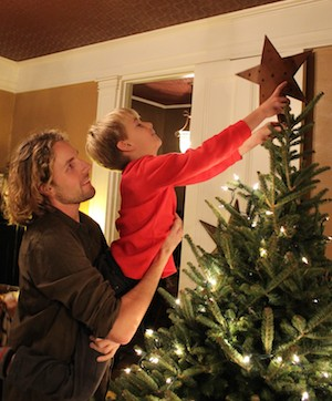 Decorating the Christmas tree, an older brother lifts his younger brother.