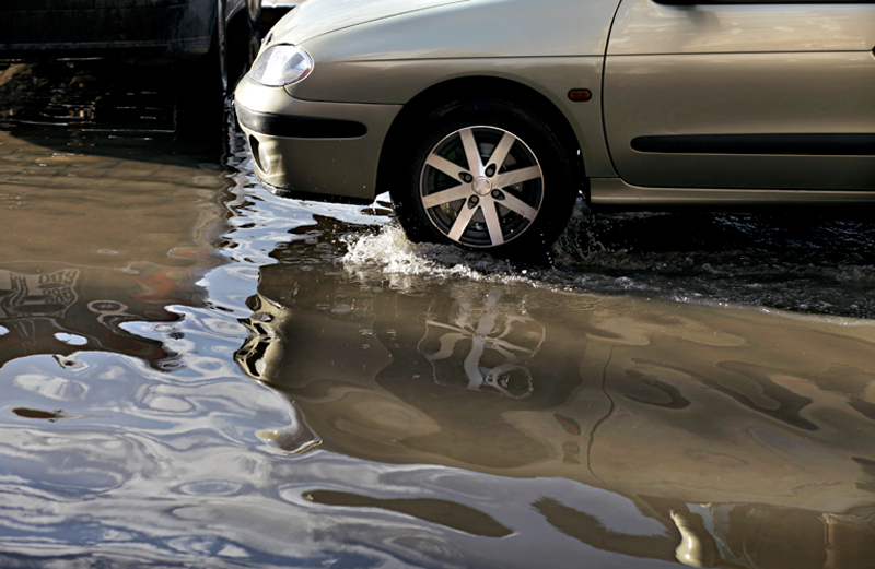 A car wades into a deep puddle.