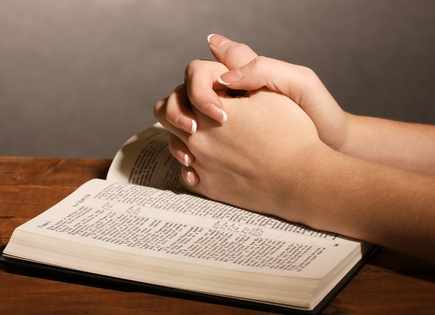 praying hands resting on a Bible