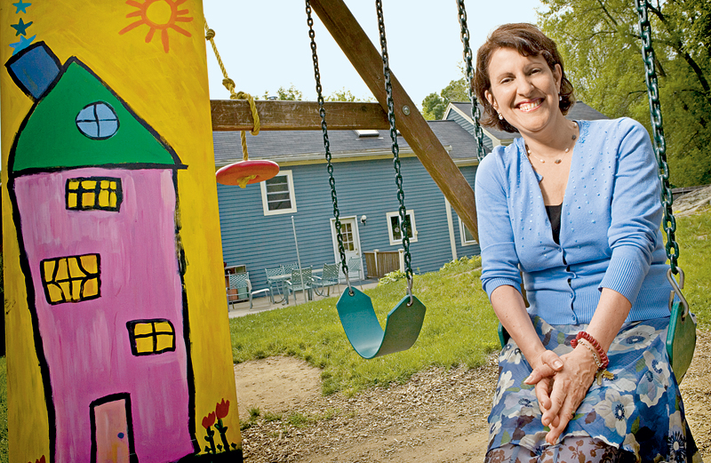 Linda Carden sits in a playground swing outside the Star House.