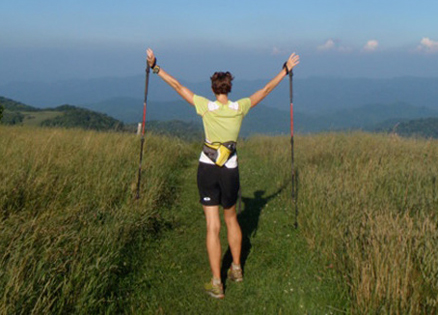 Jennifer Pharr Davis joyously raises her arms while hiking the Appalachian Trail