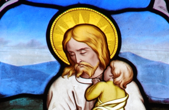 Stained glass of Jesus comforting a child