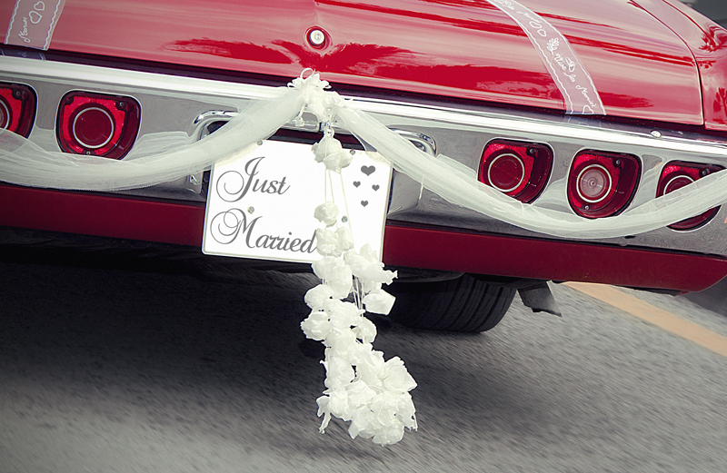 The rear bumper of a red car with a Just Married sign on it