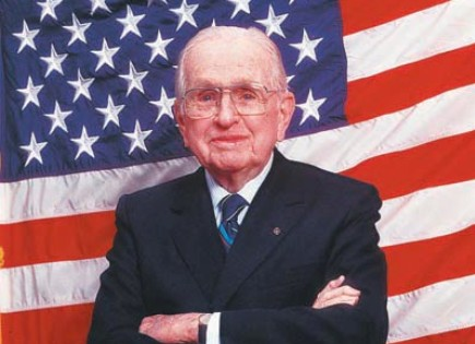 Norman Vincent Peale standing in front the US flag.