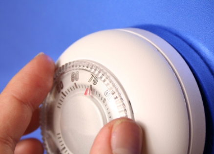 a person adjusting a thermostat