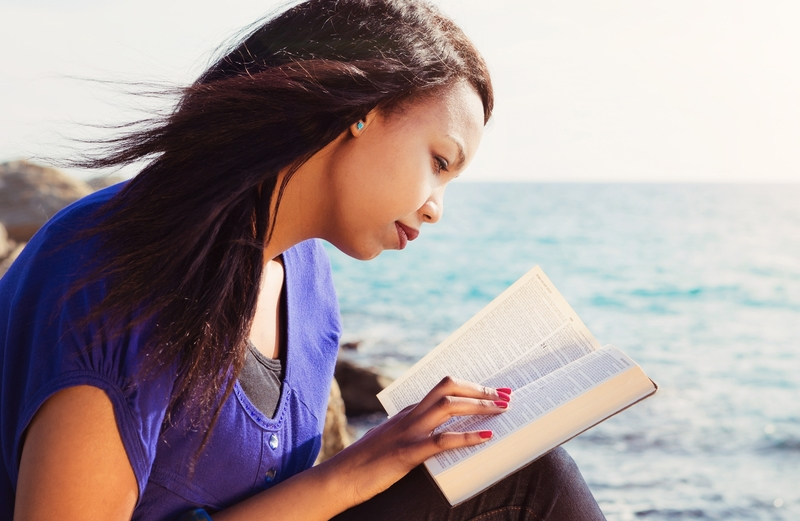 woman reading the Bible by the ocean