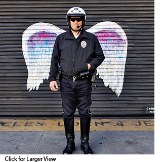 Policeman posing in front of Colette Miller's painted wings