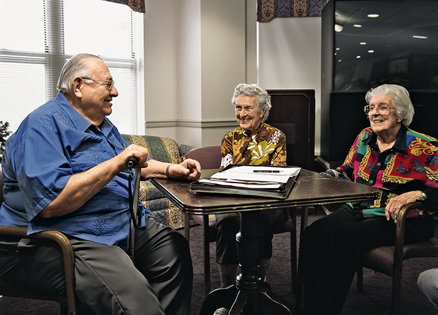 three senior citizens sitting around a table