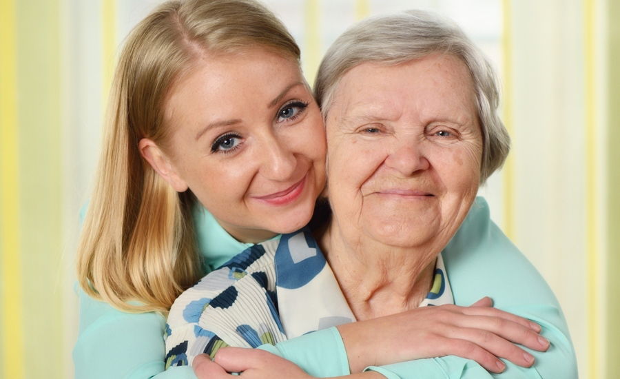 A smiling young caregiver embraces a happy senior woman.