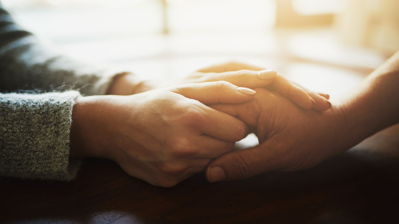 A caregiver clasps the hand of her patient