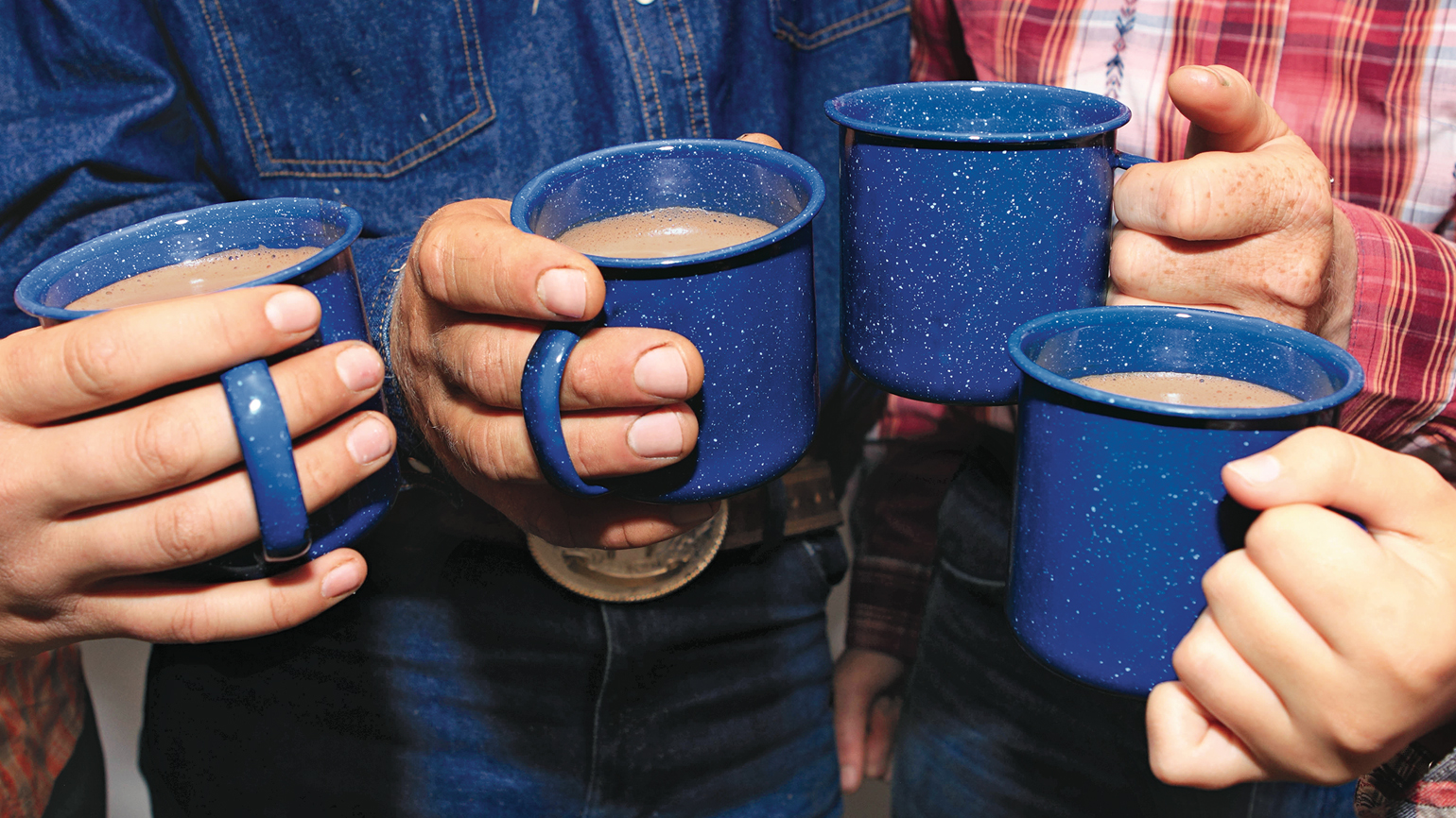 A group of ranch hands with a full cup of Mexican hot chocolate.