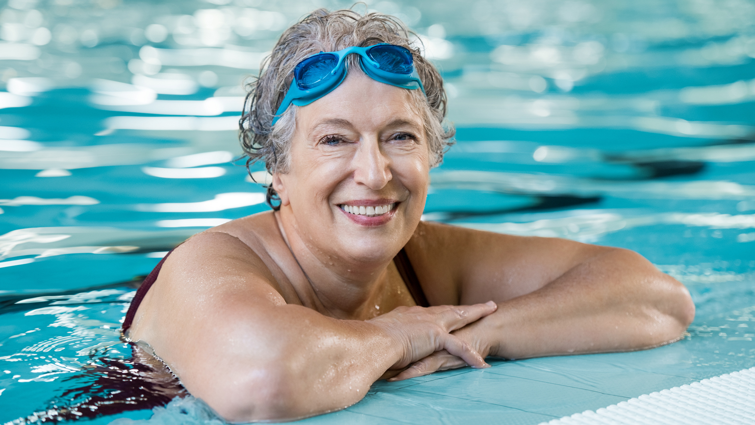 A senior citizen woman enjoying herself in the pool.
