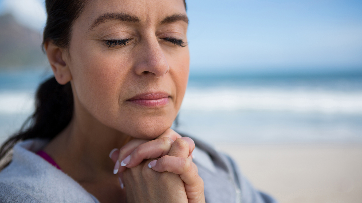 A mature woman clasps her hands in prayer