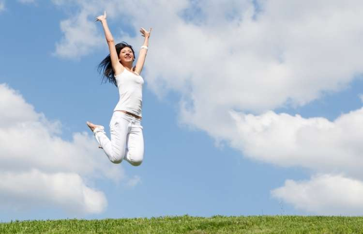 woman jumping for joy against a blue sky
