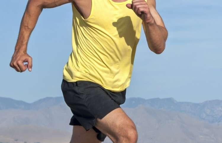 close-up of a man in a tank top and running shorts.