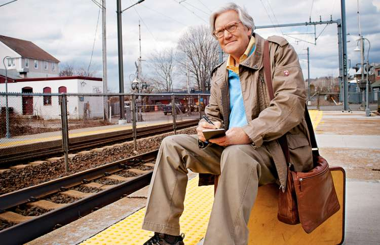 Bob Dotson sits on a suitcase on a railroad platform.