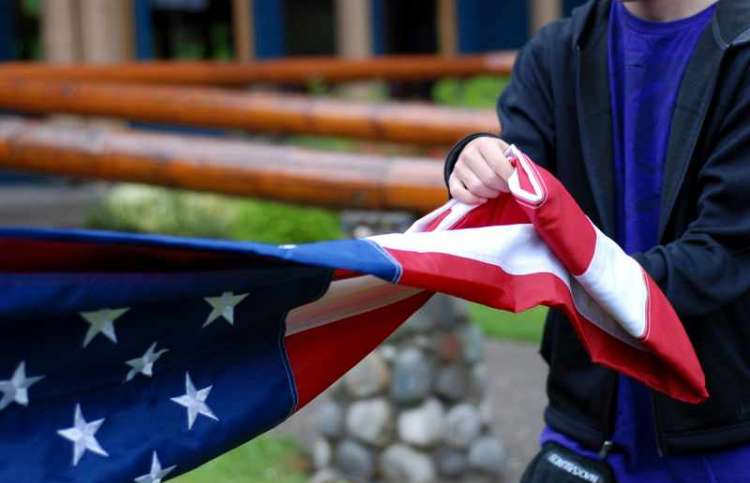 A boy folding a flag at military camp. Photo courtesy CRISTA Operation Xtreme
