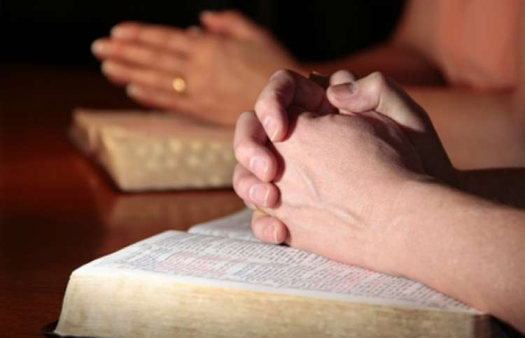 close-up of a people praying together with hands on Bibles
