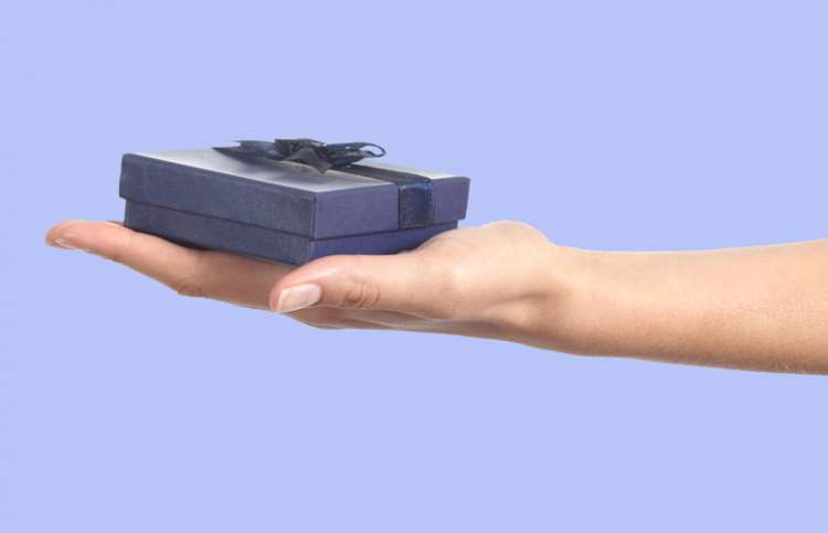 A hand reaches with a tiny blue gift box in the open palm.