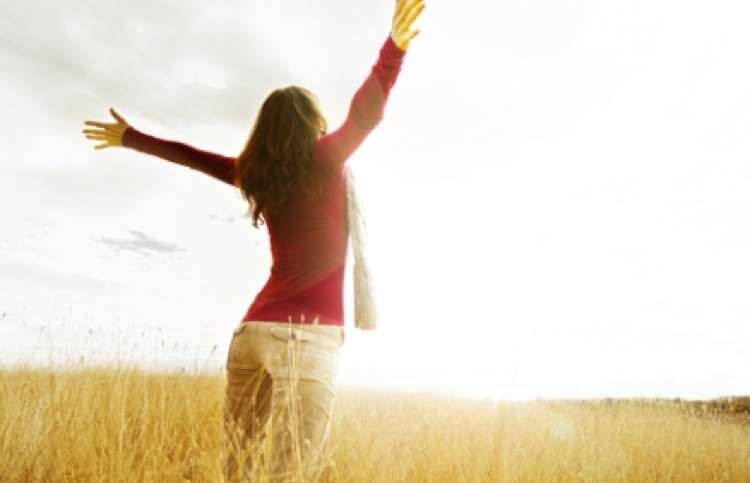 woman praising God as the sun rises