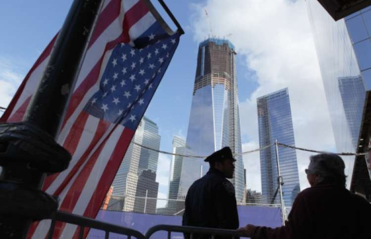 Photo of the Freedom Tower taken in spring 2013 with US flag and police officer.