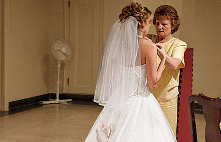 Lois helps a bride with the final adjustments to her wedding gown.