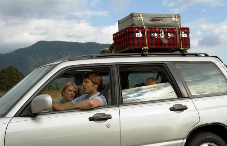 A faith-filled road trip: family in a station wagon with luggage on roof