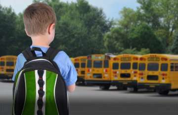 little boy in front of school buses