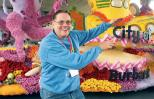 Richard Burrows poses in front of the parade float he designed.