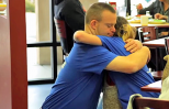 Tim embraces a customer for hug-a-thon.