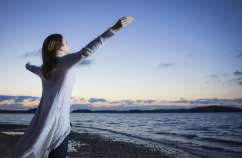 a woman with outstretched hands looks out over water willing to be obedient