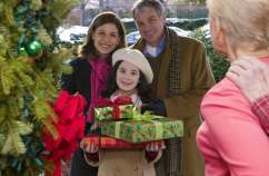 Guideposts: A smiling family bearing Christmas gifts pays a home visit to a person with cancer.
