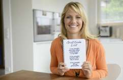 Guideposts: A smiling woman holds up her Gratitude List