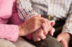A senior couple holds hands