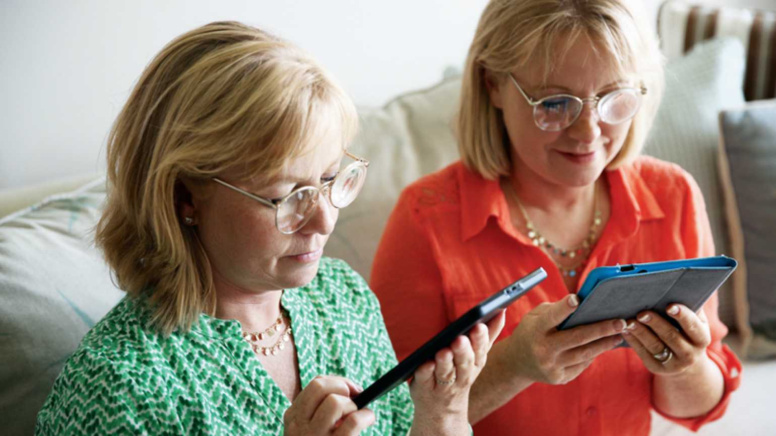 Karen (right) and Sharon in their new glasses, reading from tablets