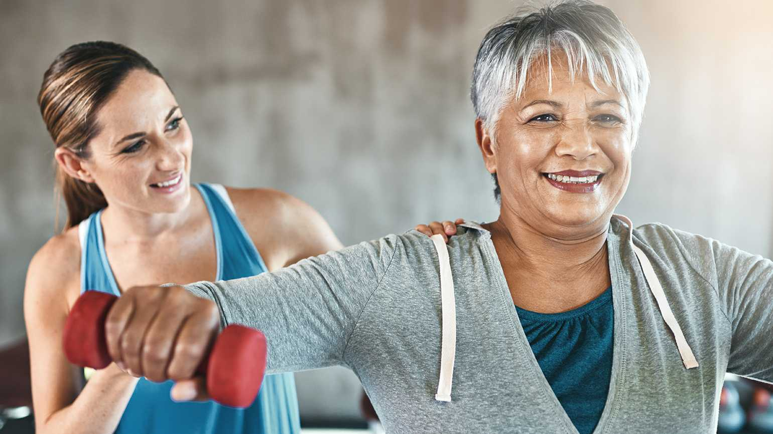 A mature woman lifts weights while her younger trainer looks on