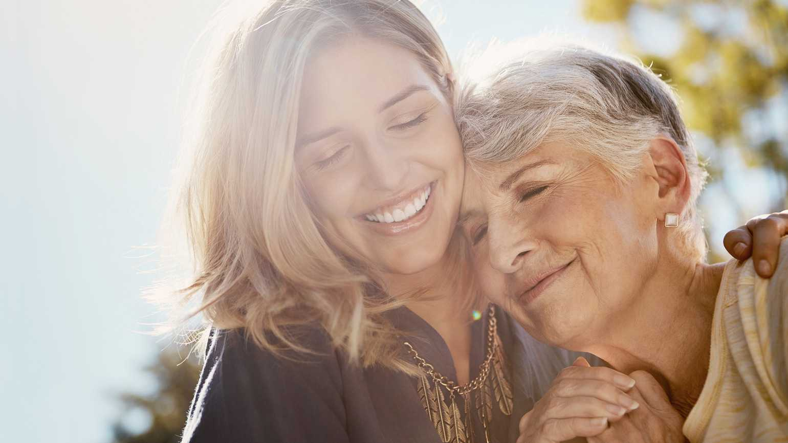 A sandwich generation daughter embraces her elderly mother with comfort.