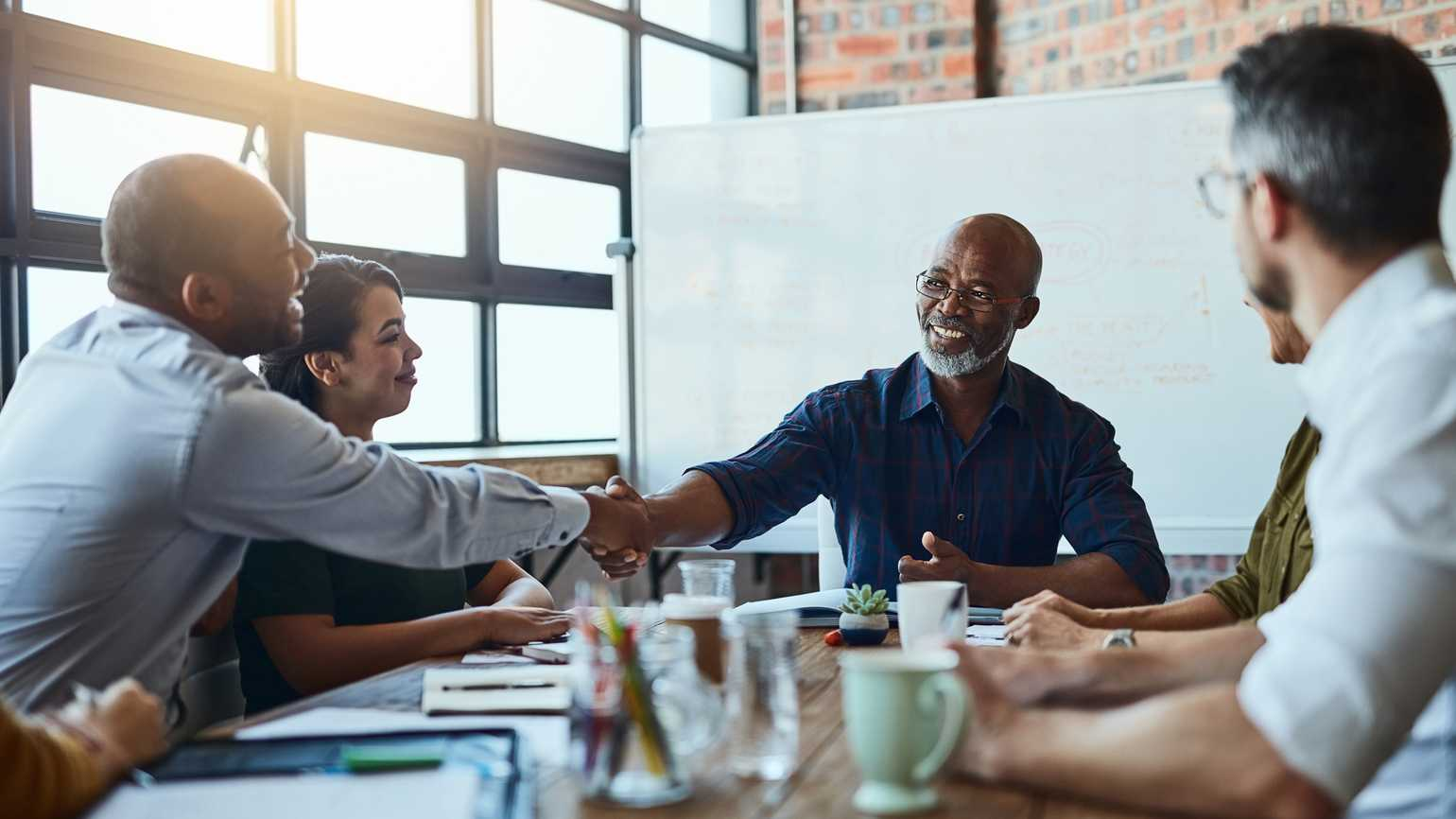 A manager shakes hands with one of his employees around a conference table.