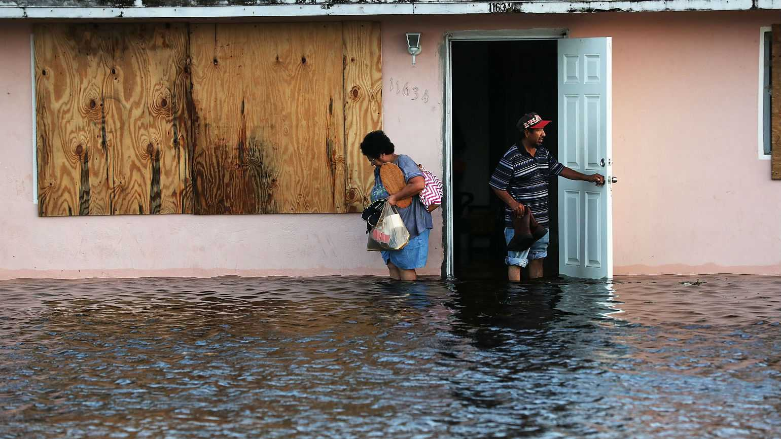 A couple leave their flooded home the morning after Hurricane Irma