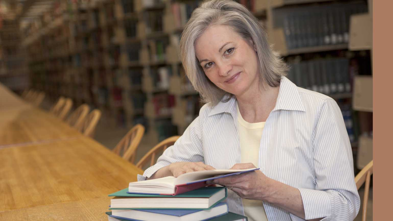 gray haired woman in a library with a stack of books