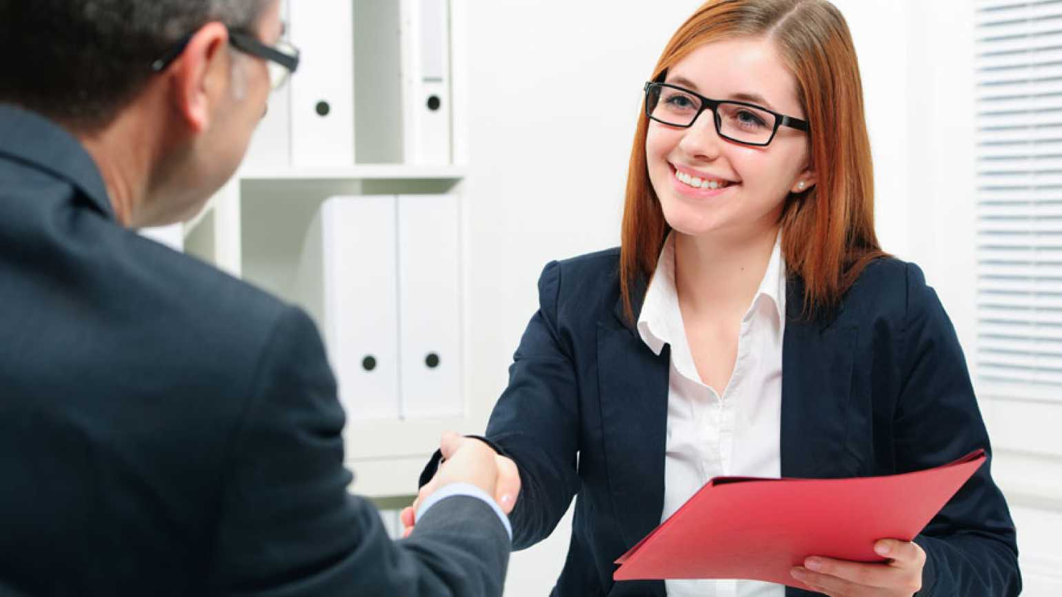 A smiling woman shakes a man's hand following a successful job interview.