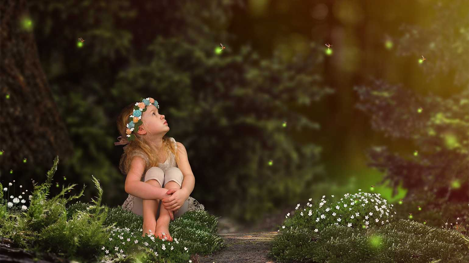 A little girl gazes up in wonder at some fireflies