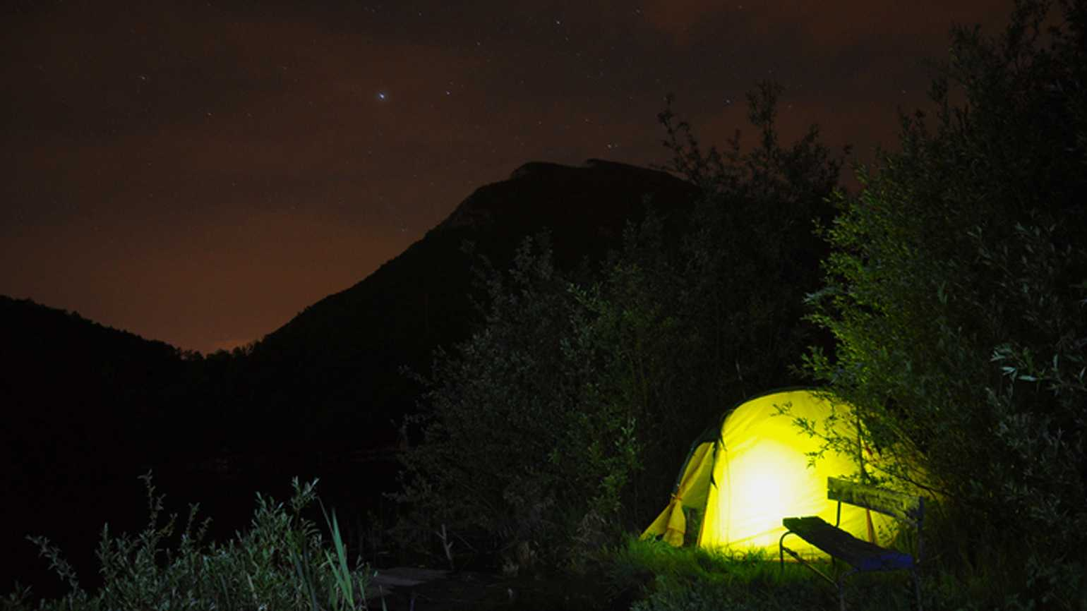 Mountainous landscape with illuminated camping tent