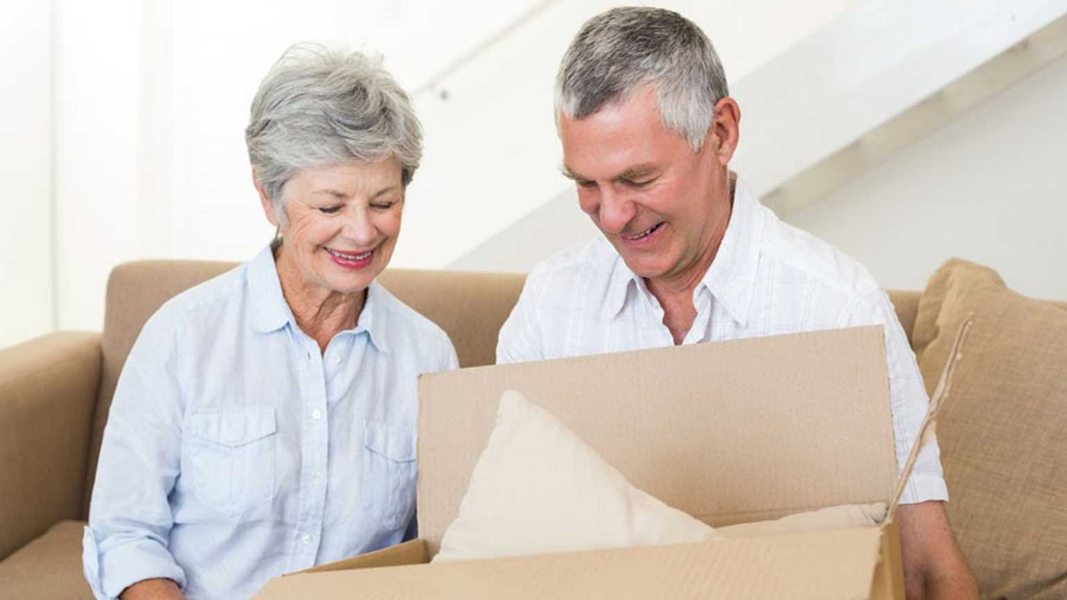 A older couple packs their belongings in moving boxes.