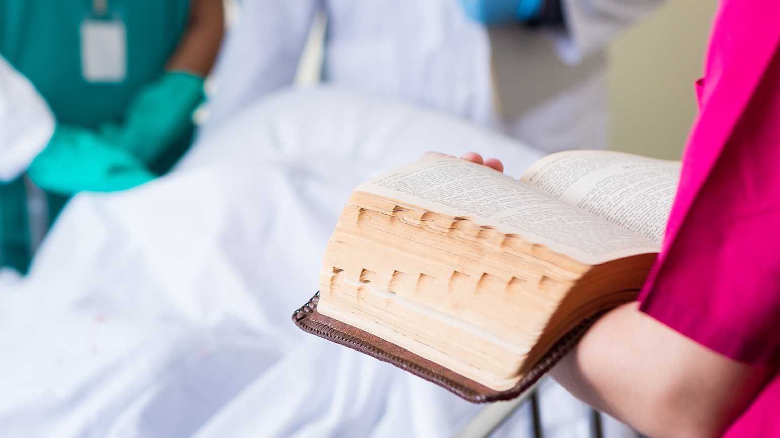 A young nurse reads the Bible for a patient