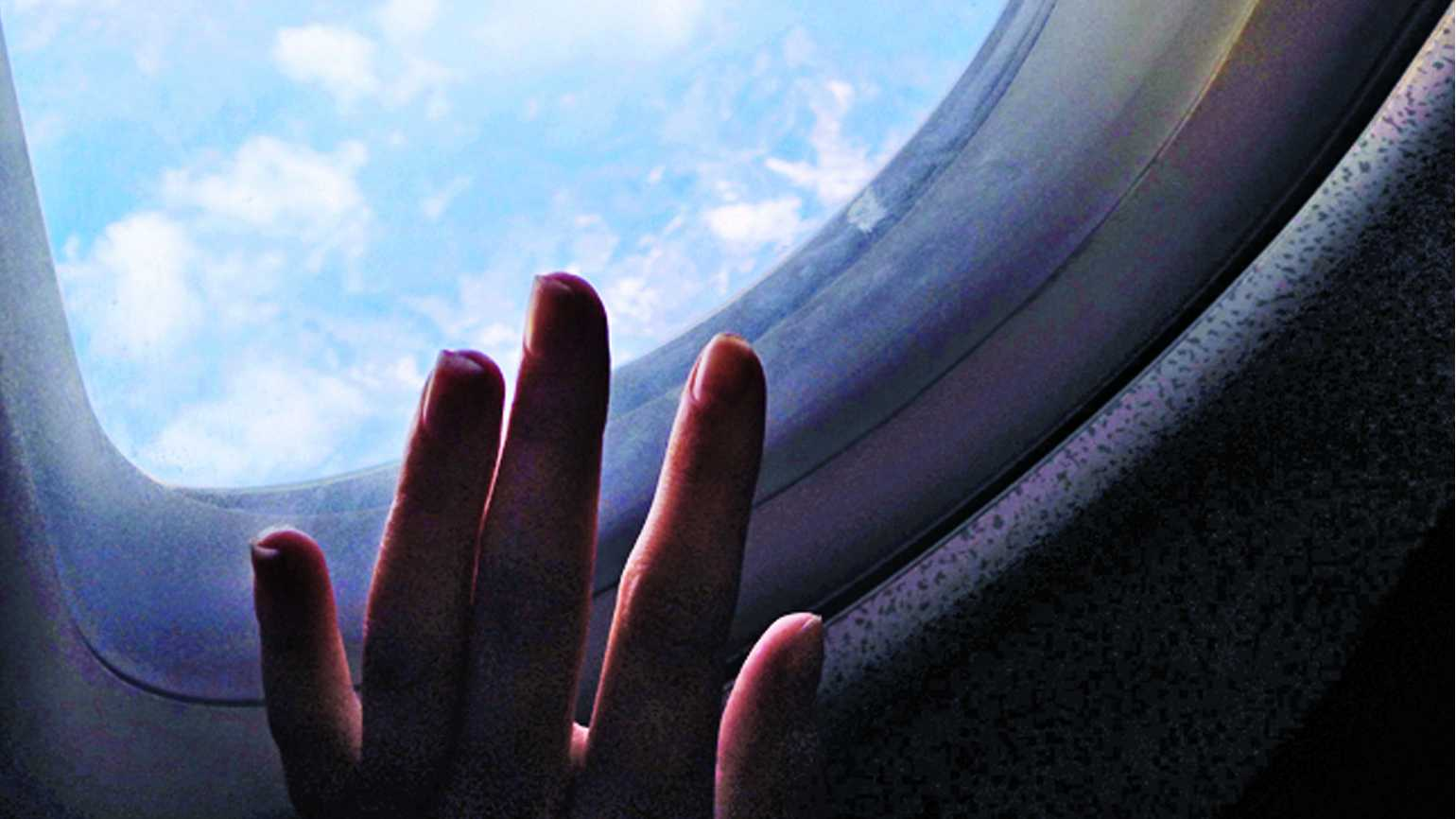 A woman's hand placed on an airplane window while in flight