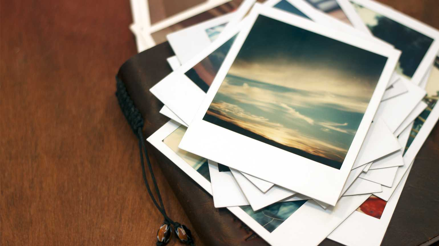 Polaroid pictures of a sunset piled on top of a leather journal.