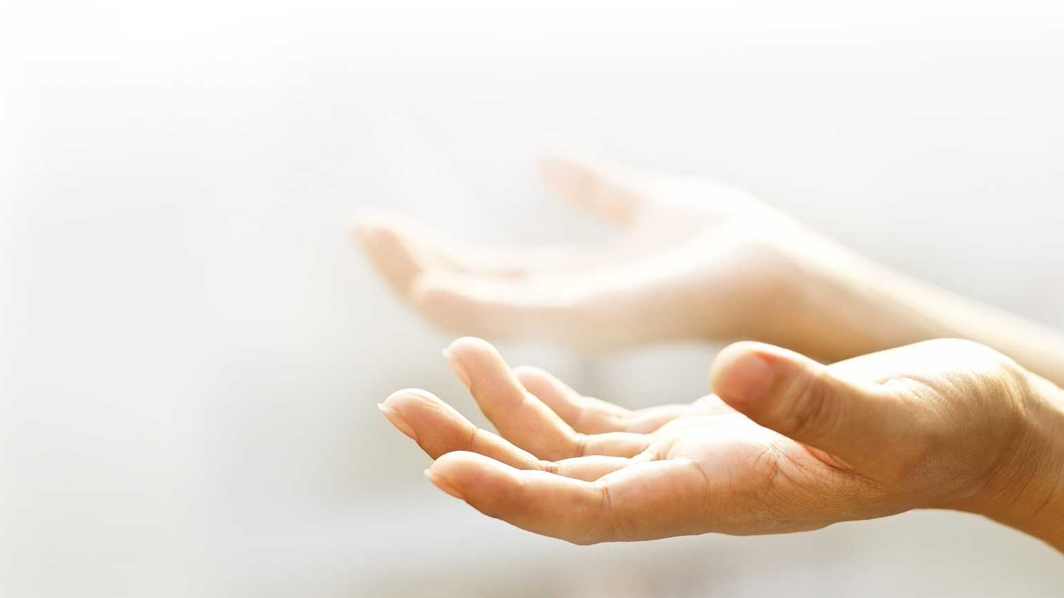 Hands illuminated by light and open in prayer.