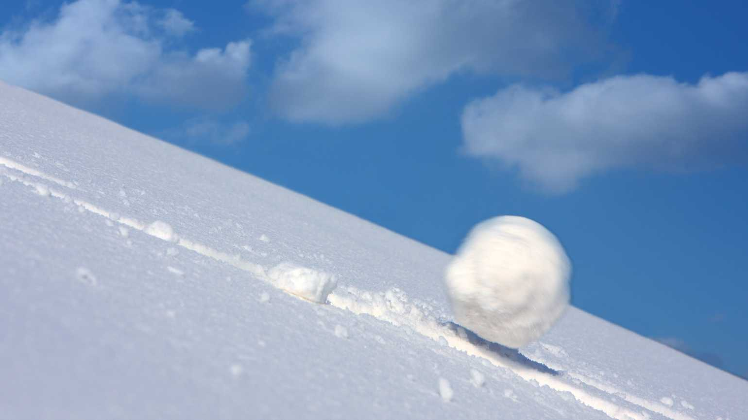 A large snowball tumbling down a snowy slope.